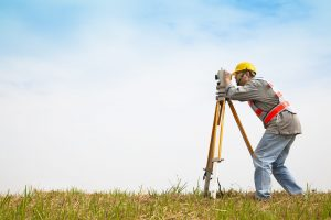 professional Surveyor engineer making measure and checking on the field